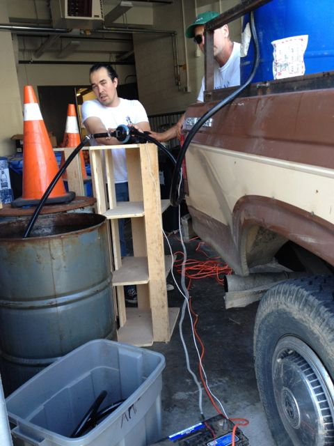 Jason Pelley and David pumping used oil into a barrel for Gertie the truck